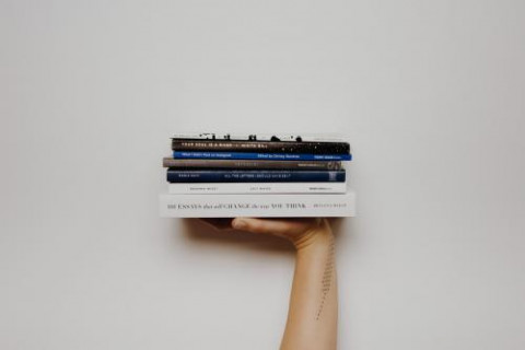 stapeltje boeken op hand